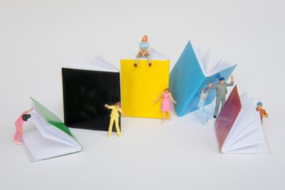 Kleine Figuren turnen um große Hefte herum