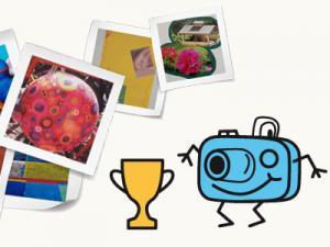 Fotoapparat Knipsi und ein goldener Pokal vor Fotografien