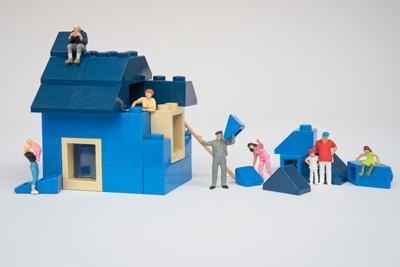 Miniaturmännchen bauen gemeinsam ein Haus