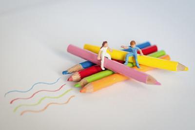 Zwei Miniaturfiguren sitzen auf bunten Stiften
