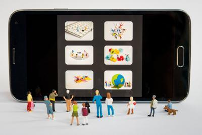 Verschiedene Miniaturmännchen stehen vor dem Display eines Smartphones
