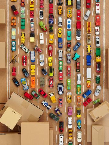 Viele bunte Spielzeugautos auf einer Pappautobahn im Stau
