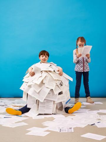 Ein Junge ist mit hunderten von Seiten bedeckt, ein Mädchen steht daneben