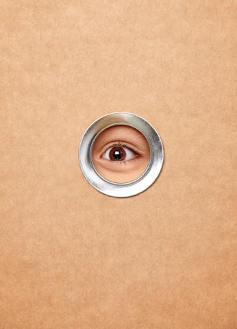Ein Auge blickt durch ein Guckloch