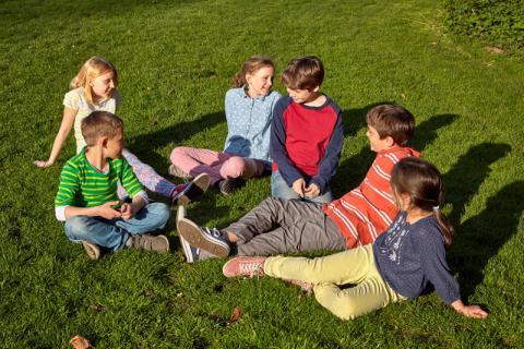 Sechs Kinder sitzen auf der Wiese