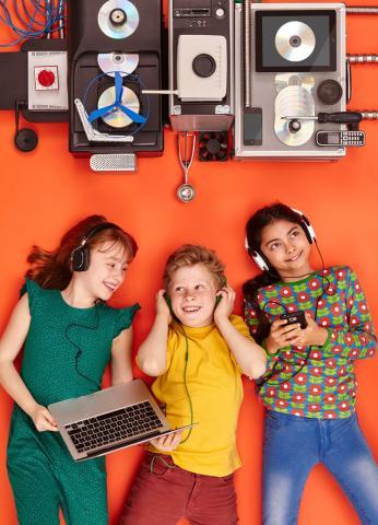 Drei Kinder mit Kopfhörern liegen auf dem Boden und hören Musik