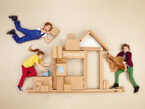 Drei Kinder bauen zusammen ein Haus aus Pappkartons