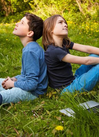 2 Jungen sitzen Rücken an Rücken im Gras und überlegen
