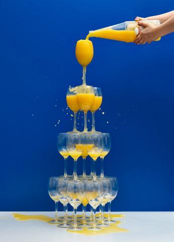 Eine Flasche Orangensaft füllt eine Gläserpyramide