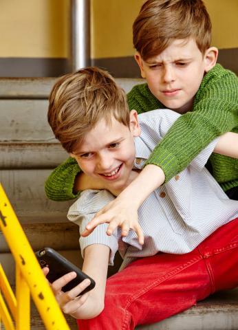 Zwei Jungen streiten sich um ein Smartphone