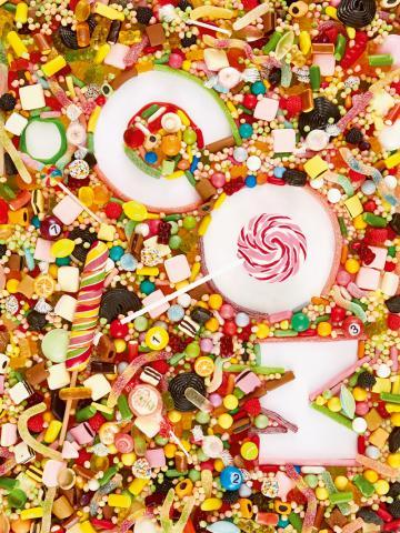 Jede Menge bunte Bonbons und Süßigkeiten mit den Buchstaben c o m in der Mitte