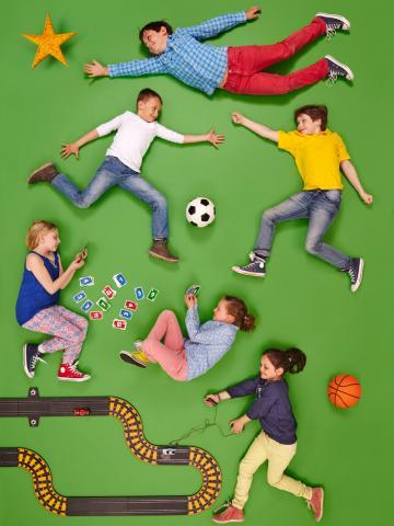 Sechs Kinder spielen Fußball, Karten und Rennautobahn