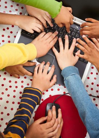 Kinderhände fassen auf eine Tastatur
