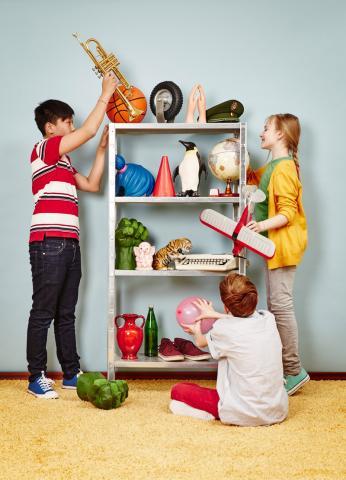 Drei Kinder bestücken ein Regal mit verschiedenen Dingen