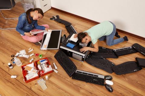 Zwei Mädchen behandeln und verarzten einen Computer mit Arztkoffer