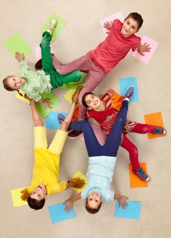5 Kinder spielen ein Freundschaftsspiel und schauen nach oben in die Kamera