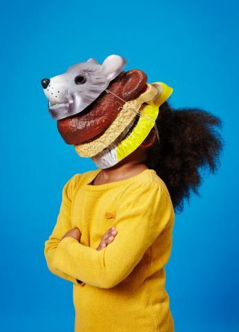 Ein Kind mit vielen Masken übereinander